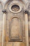 Katolsk kyrkavägg med kolonner och det runda fönstret Royaltyfria Bilder