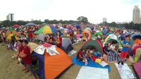 Katolska fantaster som sätts upp tält, hållvaka parkerar in, för att observera festmåltid av den svarta nazarenen stock video