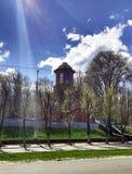 Katolska kyrkan, den blåa himlen, bak de gröna träden, i solen Arkivbild