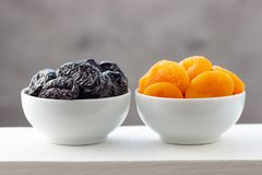 Katrinplommoner och torkade aprikors i vita bunkar fotografering för bildbyråer