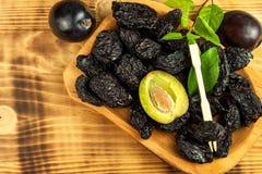 Katrinplommonet torkade plommoner bär frukt på lantlig träbakgrund Torra plommoner i en träbunke sund frukt royaltyfria foton