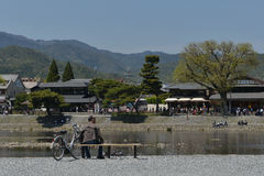 Katsura River side. Old man sits on the bench to take a break near the Katsura River under Mount Arashi Royalty Free Stock Images
