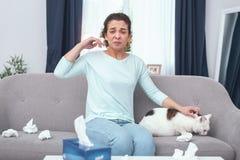 Kattägare för ung dam som är rysligt allergisk till kattpäls royaltyfri foto