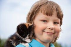 Kattunge på armen av pojken utomhus, enormt barn hans förälskelsehusdjur Arkivbilder