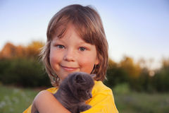 Kattunge på armen av pojken utomhus, enormt barn hans förälskelsehusdjur Arkivfoton