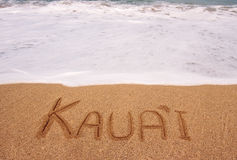 Kauai written into the sand in surging tide. White foam of the tide coming towards the name Kauai scratched in the sand royalty free stock photo