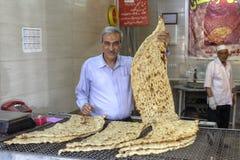 Kaufen Sie an der Bäckerei, der Bäcker, der traditionelle iranische flache Brottoilette hält Lizenzfreies Stockfoto