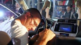 Kaufen Sie Neuwagen, sitzt Mann innerhalb des Autos und überprüft Salon in der Autoausstellung stock footage