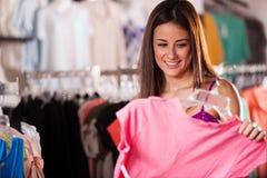Kaufen von etwas Kleidung in einem Speicher stockfotos