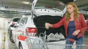 Kaufend, setzt eine Frau Taschen vom Warenkorb für den Einkauf in den Stamm des Autos ein Untertagesupermarktparken 4K stock video footage