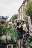 Kaufende Anlagen und Blumen der Leute am Kolumbien-Straßen-Blumen-Markt, London, Großbritannien stockbild