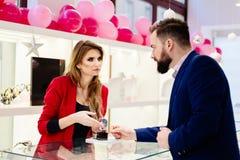 Kaufende Armbanduhr des jungen eleganten Mannes im Juweliergeschäft lizenzfreie stockfotos