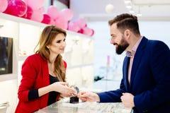 Kaufende Armbanduhr des jungen eleganten Mannes im Juweliergeschäft Lizenzfreie Stockbilder
