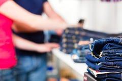 Kaufende Blue Jeans der Paare im Shop Stockbilder