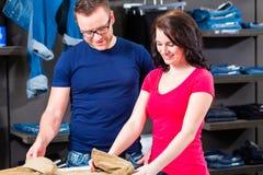 Kaufende Blue Jeans des Mannes und der Frau im Shop Lizenzfreies Stockbild