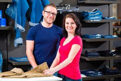 Kaufende Blue Jeans des Mannes und der Frau im Shop Lizenzfreie Stockbilder