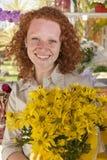 Kaufende Blumen der Frau in einem Blumenspeicher Lizenzfreies Stockfoto