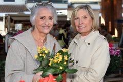 Kaufende Blumen der Mutter und der Tochter Stockfotografie