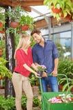 Kaufende Blumen der Paare in Garten-Center stockfoto