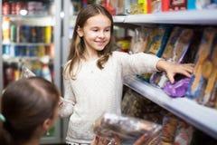 Kaufende Bonbons der Frau und des kleinen Mädchens stockfotografie