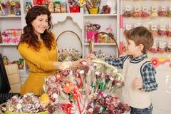 Kaufende Bonbons des glücklichen Jungen im Speicher Lizenzfreie Stockfotografie