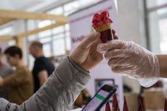 Kaufende Eiscreme des Mannes und mit unerkennbaren Leuten im Hintergrund telefonisch zahlen lizenzfreie stockbilder