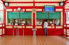 Kaufende Eisenbahnfahrkarte des Passagiers vom Fahrkartenschalter. Lizenzfreie Stockbilder
