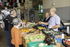 Kaufende Frucht der Leute auf dem Markt stockbild