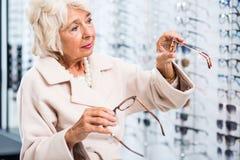 Kaufende Gläser des weiblichen Optikerpatienten Lizenzfreie Stockbilder