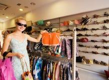 Kaufende Kleidung des blonden Mädchens stockbilder