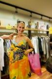 Kaufende Kleidung des blonden Mädchens in a Lizenzfreies Stockbild