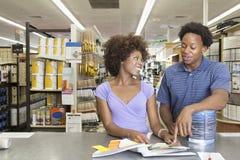 Kaufende Malereiwerkzeuge der jungen Afroamerikanerpaare am Supermarkt stockbilder
