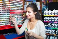 Kaufende mehrfarbige Bleistifte der fröhlichen Kundin Stockfotografie