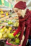 Kaufende Melone des recht weiblichen Kunden Stockfoto