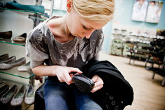 Kaufende Schuhe der Frau in einem Speicher Lizenzfreie Stockfotos
