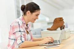 Kaufende Schuhe der jungen Frau auf Internet Stockfotografie