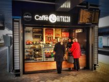 Kaufende Snäcke und Erfrischungen der Leute von einem Café auf der Plattform am Ablesen des Bahnhofs Stockfoto