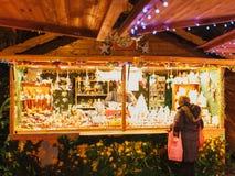 Kaufende Spielwaren und Geschenke der Frau vom Weihnachten klemmen Marktchalet fest Stockfotos