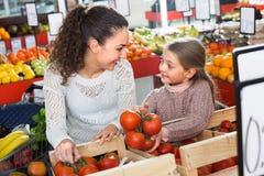 Kaufende Tomaten der Frau und des kleinen Mädchens lizenzfreie stockfotos