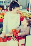 Kaufende Tomaten der Frau und des Mädchens Lizenzfreie Stockfotos