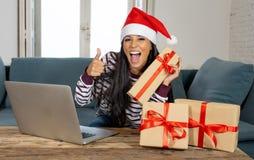 Kaufende Weihnachtsgeschenke der glücklichen attraktiven Frau, die online aufgeregt schauen stockfotos