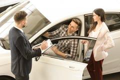 Kaufender Neuwagen der jungen Paare stockfotos
