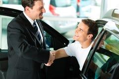 Kaufendes Auto des Mannes vom salespersonv Stockfotos