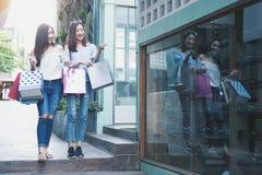 Kaufendes Einkaufszentrum mit zwei jungen glücklichen asiatischen Frauen im Freien stockbild