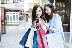 Kaufendes Einkaufszentrum mit zwei jungen glücklichen asiatischen Frauen im Freien Lizenzfreie Stockfotos