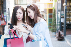 Kaufendes Einkaufszentrum mit zwei jungen glücklichen asiatischen Frauen im Freien Lizenzfreies Stockfoto