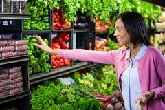 Kaufendes Gemüse der Frau im organischen Abschnitt Stockfotos