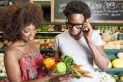 Kaufendes Gemüse der jungen Afroamerikanerpaare am Supermarkt Stockbild