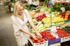 Kaufendes Gemüse der jungen Frau am Markt Lizenzfreies Stockfoto