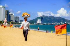 Kaufleute verkaufen lokales Lebensmittel an Touristen auf einem Strand des Meeres und der Berge Lizenzfreie Stockbilder
